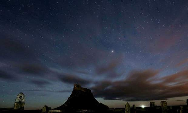 FILE- This Jan. 9, 2014, photo shows, a view of the stars above Lindisfarne Castle in Holy Island, England, Thursday, Jan. 9, 2014. Scientists reported Thursday, Nov. 6, 2014, that as many as half of all stars may lie outside galaxies. (AP Photo/Scott Heppell, File)