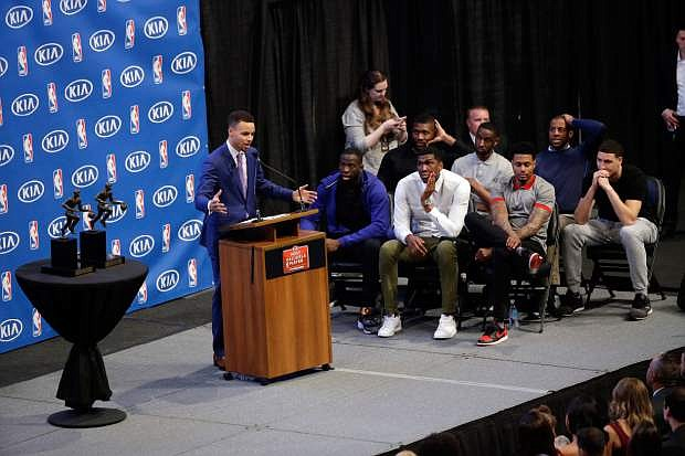 Golden State Warriors guard Stephen Curry, at left, speaks after receiving the NBA's Most Valuable Player award as his teammates watch at a basketball news conference Tuesday, May 10, 2016, in Oakland, Calif. (AP Photo/Marcio Jose Sanchez)