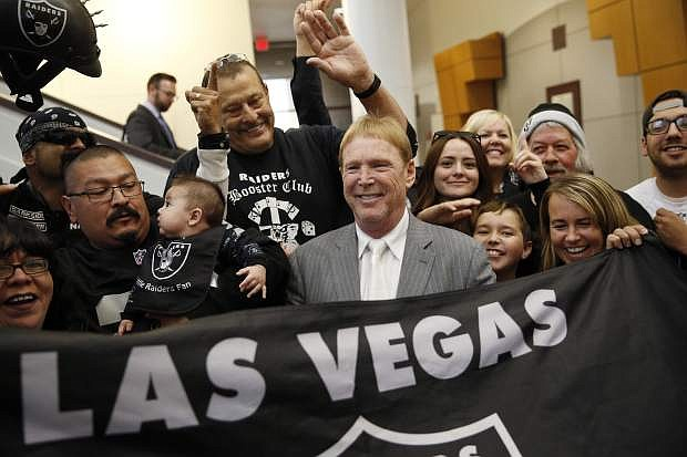 FILE - In this April 28, 2016, file photo, Oakland Raiders owner Mark Davis, center, meets with Raiders fans after speaking at a meeting of the Southern Nevada Tourism Infrastructure Committee in Las Vegas. America's most popular sport is in the midst of its greatest migration in a quarter century. In a little over a year, three NFL franchises have either moved, announced a resettlement or filed paperwork seeking to relocate. (AP Photo/John Locher, File)