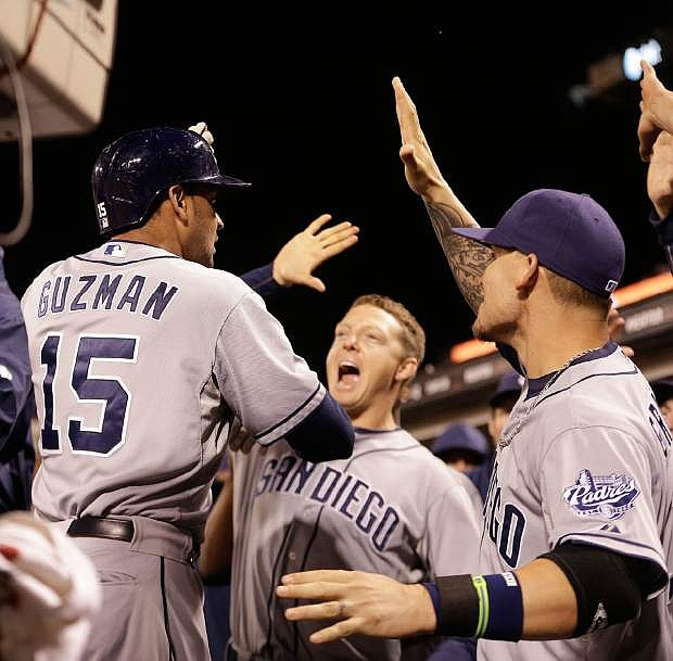 San Diego Padres' Jesus Guzman, right, is congratulated by Logan Forsythe (11) and Chase Headley (7) after Guzman hit a two run home run off San Francisco Giants' Jeremy Affeldt in the eighth inning of a baseball game Tuesday, June 18, 2013, in San Francisco. (AP Photo/Ben Margot)