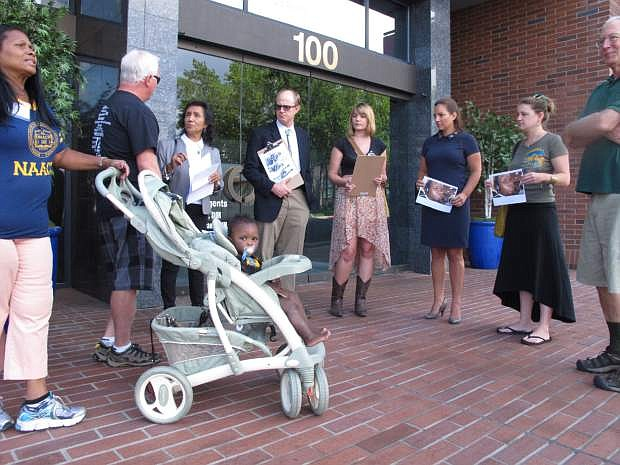 Pat Gallimore, left, second vice president of the Reno-Sparks NAACP, with her grandson, Boston; Theresa Navarro, third from left, chairwoman of the Nevada Progressive Alliance of Nevada; and Bob Fulkerson, center, PLAN's state director, were among those who delivered a letter to the U.S. attorney's office in Reno, Nev., Monday, Aug. 25, 2014, calling for the firing of the Ferguson police officer who shot Michael Brown in Missouri and urging Attorney General Eric Holder to launch a nationwide investigation of police brutality and harassment in minority communities. (AP Photo/Scott Sonner)