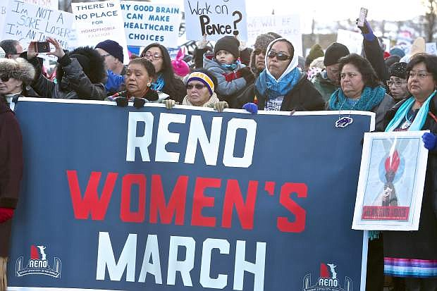 A group of Native American women hold a banner in downtown Reno Saturday morning.