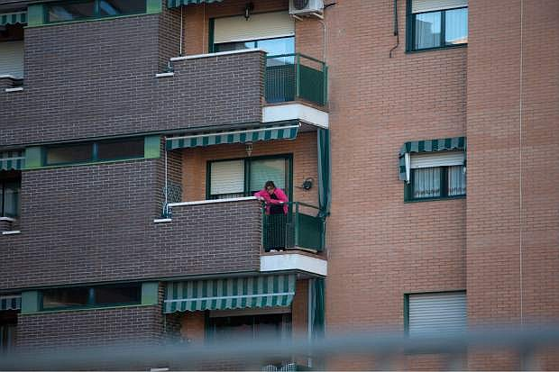 A neighbor looks down from a balcony of a housing estate, where it is believed the nursing assistant who was tested positive for Ebola and her husband live in Madrid, Spain,Tuesday, Oct. 7, 2014. Three more people were placed under quarantine for Ebola at a Madrid hospital where a Spanish nursing assistant became infected, authorities said Tuesday. More than 50 other possible contacts were being monitored. The nurse, who had cared for a Spanish priest who died of Ebola, was the first case of Ebola being transmitted outside of West Africa, where a months-long outbreak has killed at least 3,500 people and infected at least twice as many. (AP Photo/Paul White)