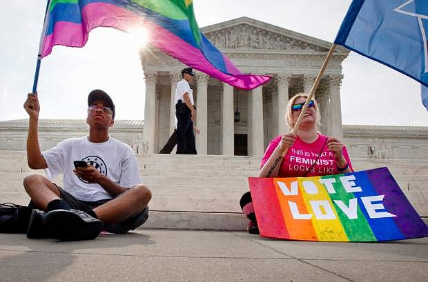 Carlos McKnight, 17, of Washington, left, and Katherine Nicole Struck, 25, of Frederick, Md., hold flags in support of gay marriage as security walks behind outside of the Supreme Court in Washington, Friday June 26, 2015. A major opinion on gay marriage is among the remaining to be released before the term ends at the end of June.  (AP Photo/Jacquelyn Martin)