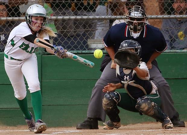 The Lady Wave's Izzy Thomas bunts while the Grizzlies' catcher Vivian Quiroz-Montano looks on.