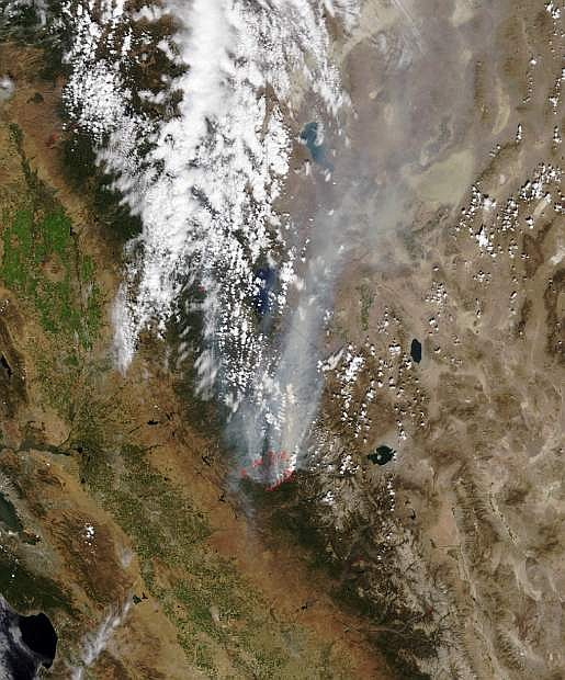 In this Monday, Aug. 26, 2013 satellite photo released by NASA, a smoke plume trails north from the drought-fueled Rim Fire, center, burning near Yosemite National Park in central California. Red outlines indicate hot spots where the satellite detected unusually warm surface temperatures associated with fires. Containment of the fire more than doubled to 15 percent, although it was within a mile of the park's Hetch Hetchy Reservoir, the source of San Francisco's famously pure drinking water, officials said. (AP Photo/NASA)