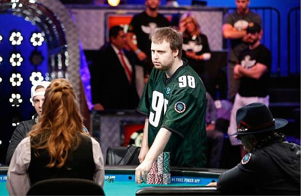 Joseph McKeehen stands at his seat at the World Series of Poker Sunday, Nov. 8, 2015, in Las Vegas. Sunday night was the first of three days of poker-playing before crowning a new champion and awarding more than $7 million to the winner. (AP Photo/John Locher)