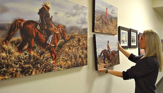 Churchill County's Julie Guerrero hangs work by photographer Dennis Doyle for the upcoming open house. Self-taught with 20 years' experience, local artist Doyle captures images throughout the west.