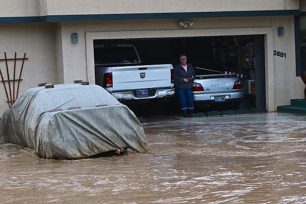 Patricia Miskella stands behind sand bags in her garage on Kayne St. Wednesday.