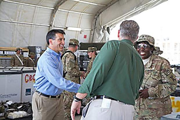Governors Brian Sandoval, left, and Jay Nixon, Missouri, meet with a soldier in Afghanistan this weekend.