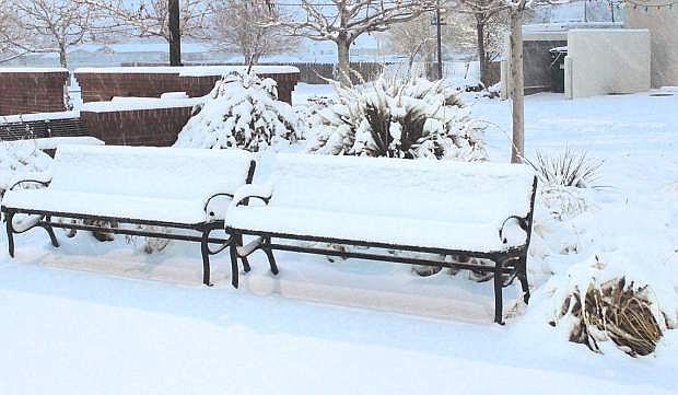 Snow covers a bench at Millennium Park.