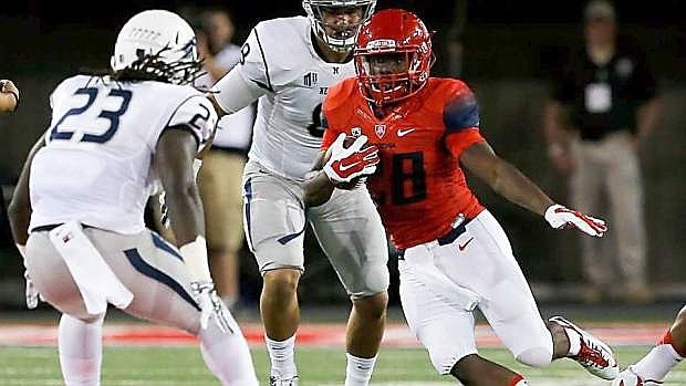 Arizona's Nick Wilson runs against the Wolf Pack defense in Tucson..