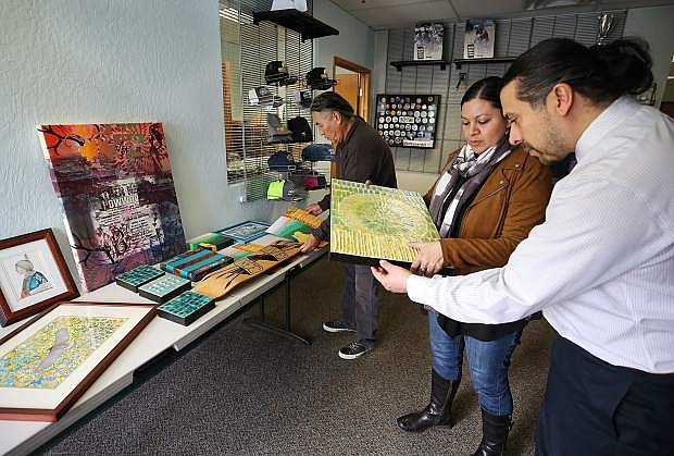 Carson City Arts and Culture Coordinator Mark Salinas, right, talks with Great Basin Native artists Melissa Melero-Moose and Ben Aleck in Carson City, Nev. on Wednesday, Feb. 1, 2017. The Carson City Visitors Bureau is hosting the show February through June, featuring five Native American artists. The public is invited to an opening reception Friday, Feb. 3 from 5-7 p.m. Photo by Cathleen Allison/Nevada Photo Source