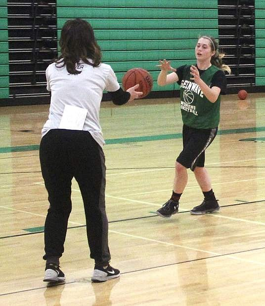Coach Anne Smith, left, passes the ball to Kenna Hamlin during a drill at a Lady Wave practice earlier this season.