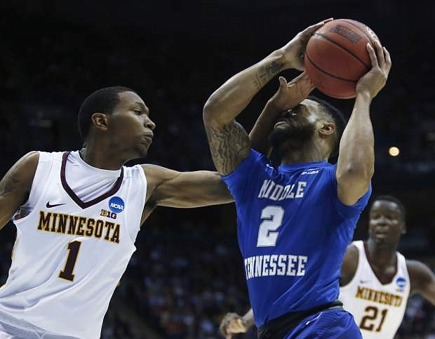 Middle Tennessee State's Antwain Johnson (2) is hit in the face as he drives past Minnesota's Dupree McBrayer (1) during the first half of an NCAA college basketball tournament first round game Thursday, March 16, 2017, in Milwaukee. (AP Photo/Kiichiro Sato)