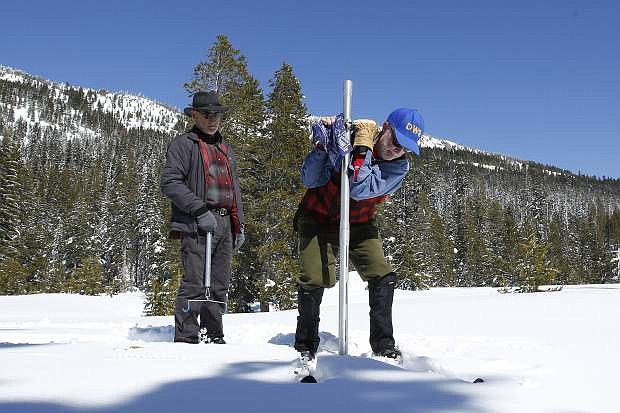 FILE - In this March 1, 2017 file photo, Frank Gehrke, right, chief of the California Cooperative Snow Surveys Program for the Department of Water Resources, plunges the survey tube into the snowpack as he conducts the third manual snow survey of the season at Phillips Station near Echo Summit, Calif. Surveyors will crunch across the deepest mountain snowdrifts California has seen in years on Thursday, March 30, 2017, to take the first snow measurement of the spring, a time when the snow begins to melt and flow downhill. (AP Photo/Rich Pedroncelli, File)