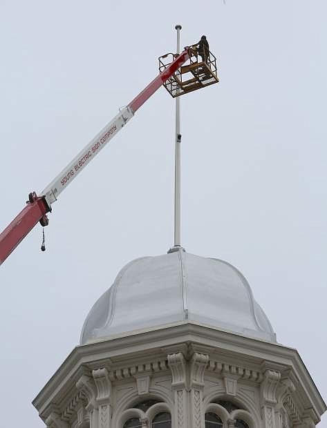 Tom Pierce attempts to repair the flag pole on top of the Capitol dome Tuesday morning, but high winds forced Pierce back to the ground before repairs could be made.
