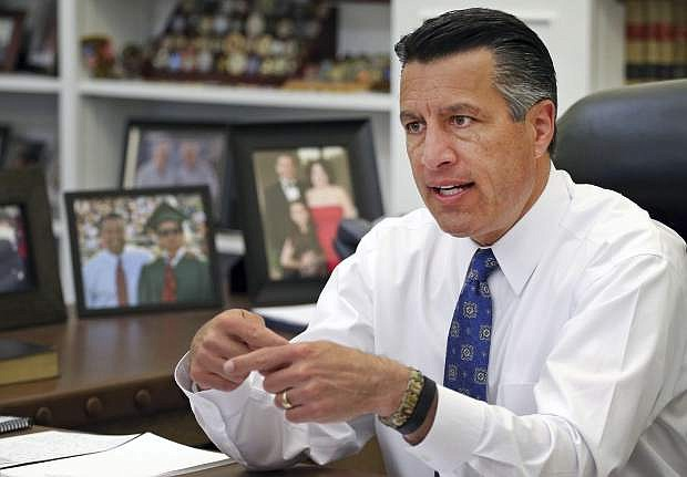 In this April 17, 2015, file photo, Nevada Gov. Brian Sandoval sits in his office at the Capitol in Carson City.