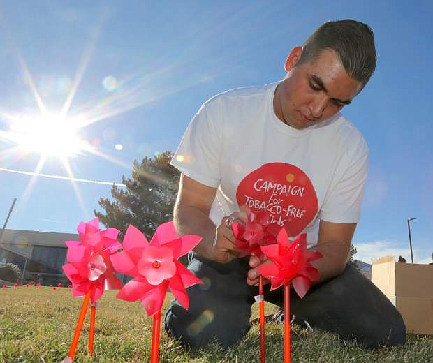 """Western Nevada College student and """"Kick Butts Day"""" event coordinator Spencer Flanders sticks pinwheels into the front lawn of the campus on Tuesday afternnon."""