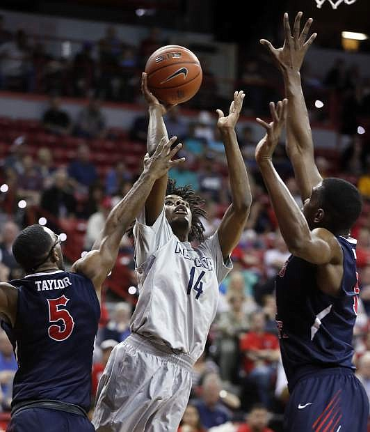 Nevada's Lindsey Drew shoots as Fresno State's Jahmel Taylor, left, and Bryson Williams defend during the first half of an NCAA college basketball game in the Mountain West Conference tournament semifinals Friday, March 10, 2017, in Las Vegas. (AP Photo/Isaac Brekken)