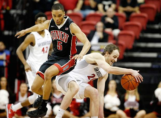 UNLV's Jalen Poyser (5) and San Diego State's Matt Shrigley go after a loose ball during the second half of an NCAA college basketball game in the Mountain West Conference tournament Wednesday, March 8, 2017, in Las Vegas. San Diego State defeated UNLV 62-52 in overtime. (AP Photo/Isaac Brekken)