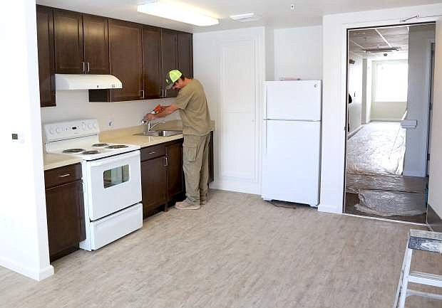 Adam Glass with Q&D Construction does finish work in one of the new apartment units at Richards Crossing on Monday.