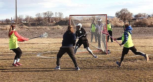 Goalie Audrey Rasmussen defends the goal as Jaidyn Delgado, left, Maiya Swan, center foreground, and Jaylee McEwen attack.