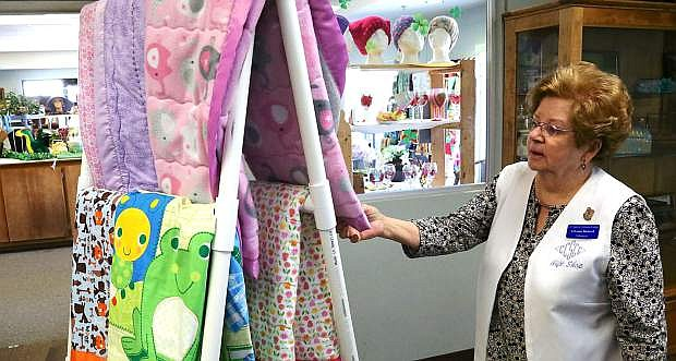 Volunteer LaVonne Birdwell arranges quilts on a stand located near the Senior Center gift shop that is open to the public.