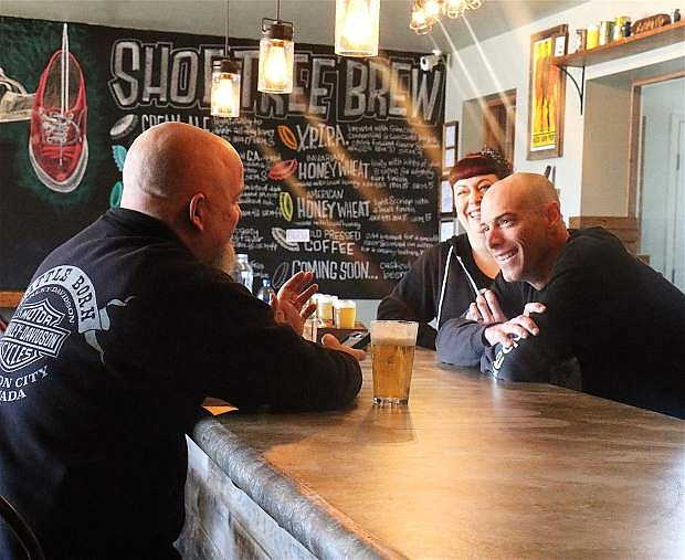 Jeff and Jessica Young talk to a customer at the Shoe Tree Brewing Company bar and tasting room.
