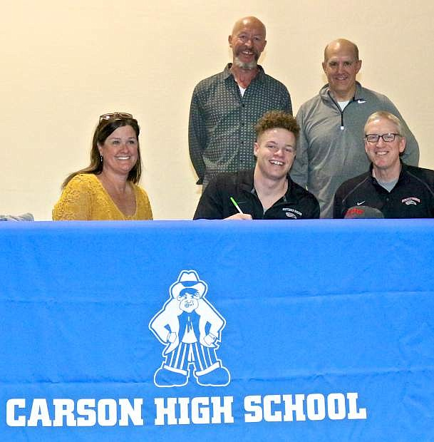 Tez Allen, center, signs his letter of intent to play basketball at Southern Oregon University in Ashland, Or. Thursday at Carson High. Pictured with him are his mother Kaylie Rooker (left), father Roswell Allen and CHS boys coach Carlos Mendeguia (standing) and SOU basketball coach Brian McDermott (seated).