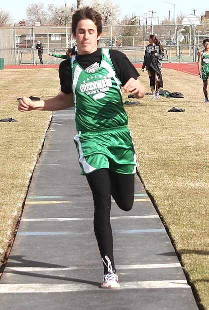 X prepares to kick off the end of the path during the long jump event.