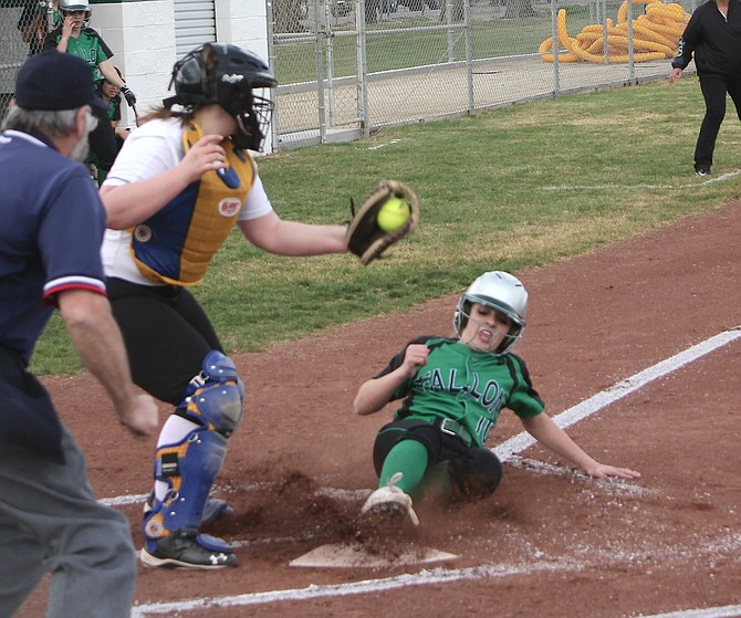 Shelbi Schultz slides into home plate under South Tahoe catcher Drue Chapman's arm.