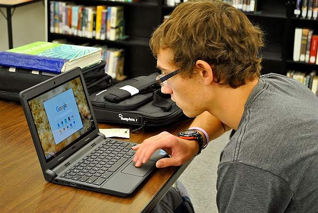 Churchill County High School junior Thomas James starts work on his Google Chromebook during a study hall period.