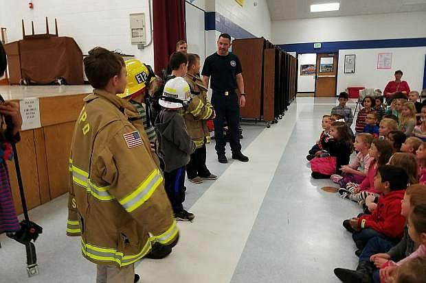 Students at Pinion Hills Elementary School try on firefighter apparatus during a school assembly where they presented members of the East Fork Professional Firefighters association $2,116.98 they raised by collecting loose change.
