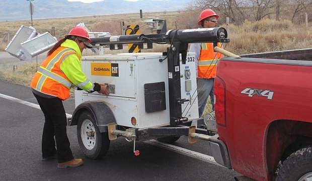 Flaggers hook up portable lights before U.S. Highway 95 reopened Wednesday afternoon.