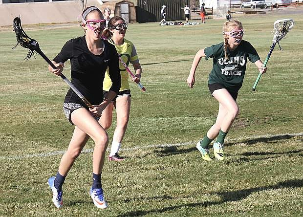 Sadie O'Flaherty, left, Jaidyn Delgado and Aubrey Renfroe, right, carry balls as they race across the field.