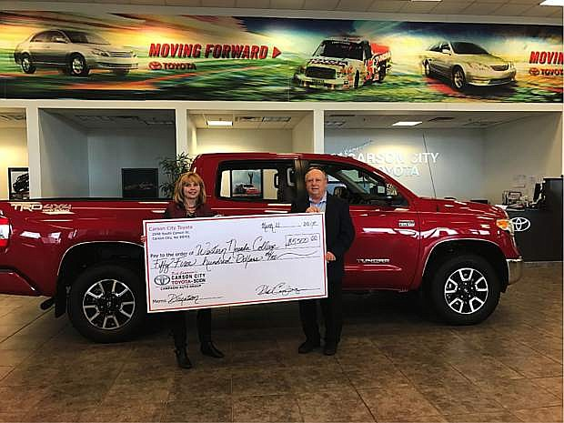 Niki Gladys, WNC Foundation executive director, accepts a donation from Dana Whaley, general manager Carson City Toyota. The donation will be used toward the Dick Campagni Automotive Scholarship fund.