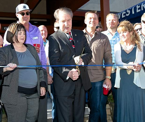 Mayor Bob Crowell is flanked by supervisors Lori Bagwell and Karen Abowd Thursday evening as the ribbon is cut on the newly re-furbished Battle Born office complex on Division St. in Carson.
