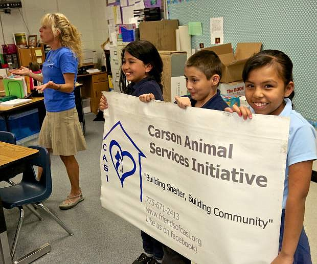 CASI Executive Director Lisa Schuette speaks to Nancy Cole's 3rd graders at Empire Elementary Friday while employing the help of three students to hold her sign.