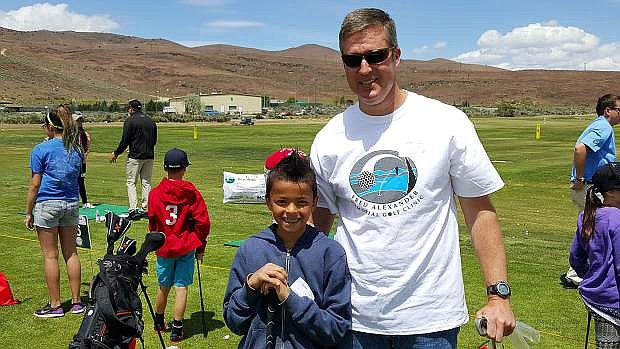 """Last year's """"special golf club winner"""" and his dad during the Fred Alexander Memorial Family Golf Clinic."""
