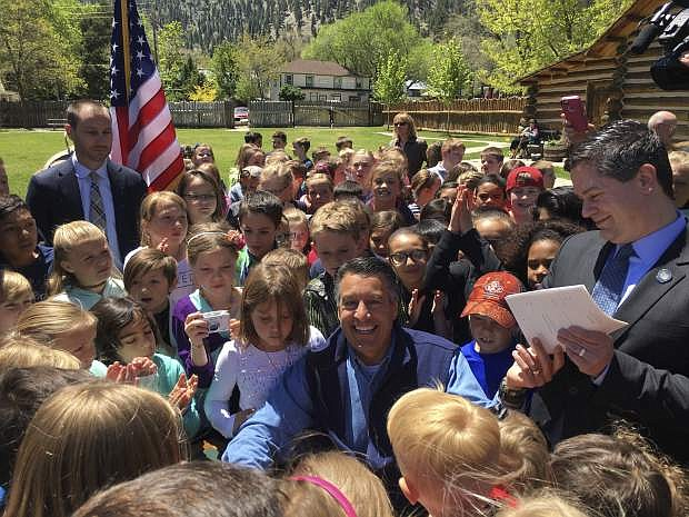 Nevada Gov. Brian Sandoval smiles after signing Assembly Bill 385 expanding free parks admission for elementary students at Mormon Station State Historic Park in Genoa, Nev., Friday, May 12, 2017. Under the law, Nevada students ages 9-11 can play at state parks for free beginning in July. The measure builds on a federal program that allows fourth-graders to apply for free admission to all national parks and Nevada state parks. (AP Photo/Alison Noon)