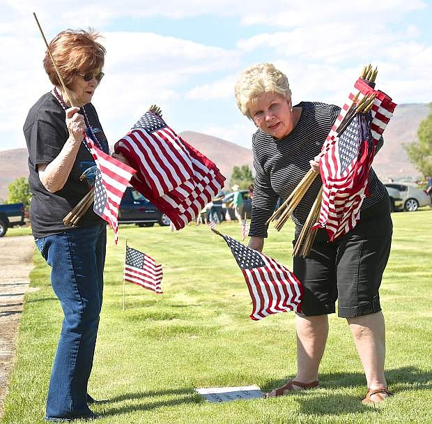 Karyl Summers and Sue Barnett, both of Carson City, place American flags on service men and women's headstones Friday.