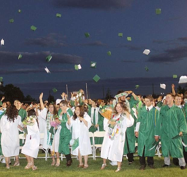 The Churchill County High School class of 2017 toss their graduation caps to the wind Friday night on the Edward Arciniega Athletic Complex's football field.