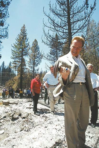 Dan Thrift/Tahoe Daily Tribune California Governor Arnold Schwarzenegger finds a dumbell in the remains of an Angora Fire home on View Circle while taking a tour of the area Wednesday afternoon.