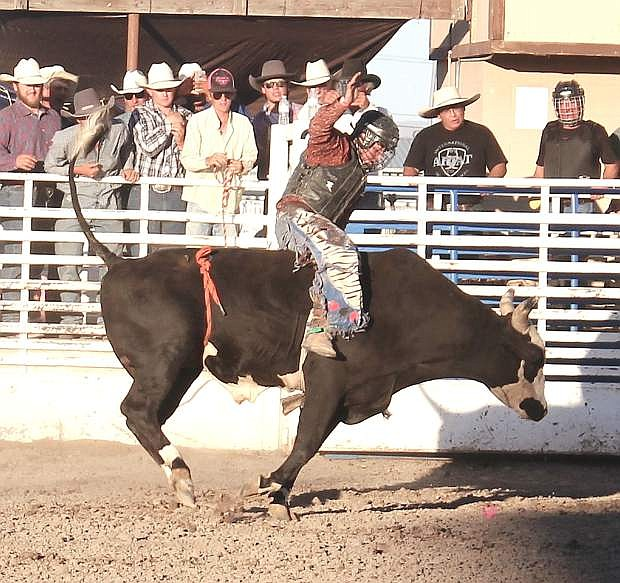 Billy Quillan hangs on as his bull tries to buck him off.