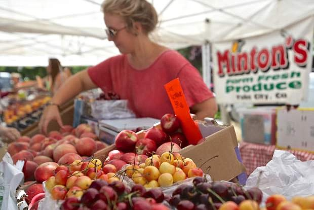 Cheyenna Burrows of Minton Farm Fresh out of Yuba City, Calif. arranges fruit at their booth at last year's 3rd & Curry Street Farmer's Market.