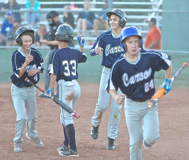 The Carson 12-year-old All-Stars congratulate each other at home plate after going up 7-0 over Reno Centennial in the first inning Wednesday night.