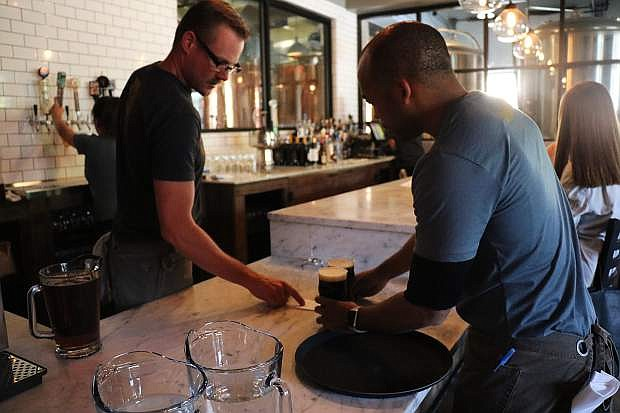 Bartender Neill Beurskens, left, hands drinks to server Kelson Powell during Monday night's soft opening at The Union.