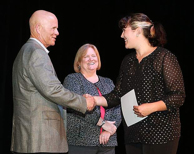 Western Nevada College Dean of Student Services John Kinkella and Nancy Olsen congratulate graduate Willow Bartels during a ceremony as more than 100 students received their High School Equivalency during a Western Nevada College ceremony on June 19.