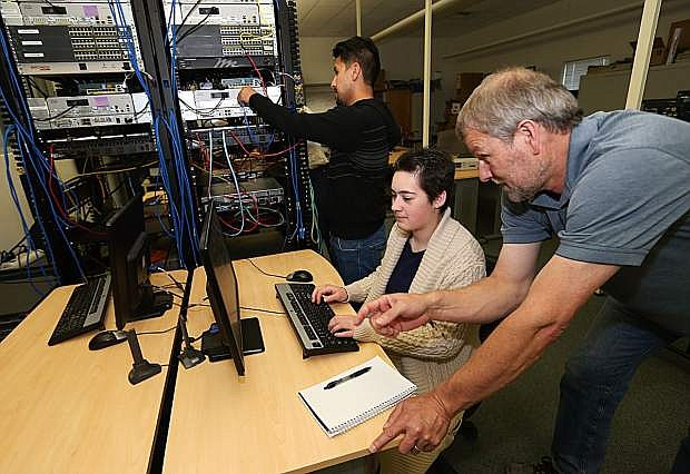 CISCO Technology Instructor Dave Riske works with students Sergio Teutli, rear, and Chrissa Johnson at Western Nevada College in Carson City, Nev., on Wednesday, April 27, 2016. Photo by Cathleen Allison